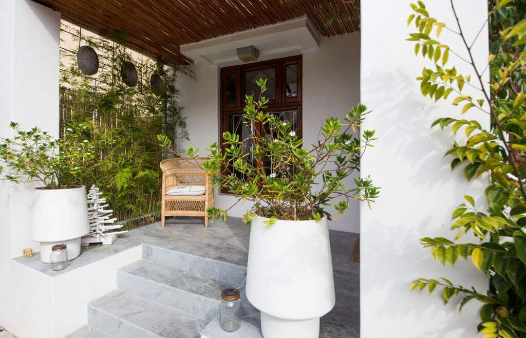 house garden entrance with flower pots and chair